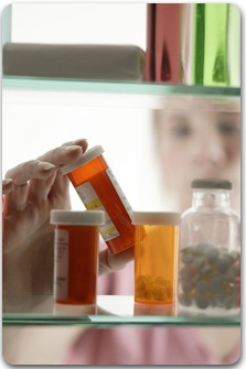 A Woman taking a bottle from a drug cabinet - You are on a CIGNA Medicare Rx page