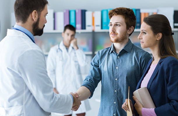 Young couple shaking hands with doctor