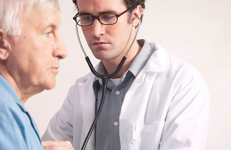 Doctor using stethoscope on senior man