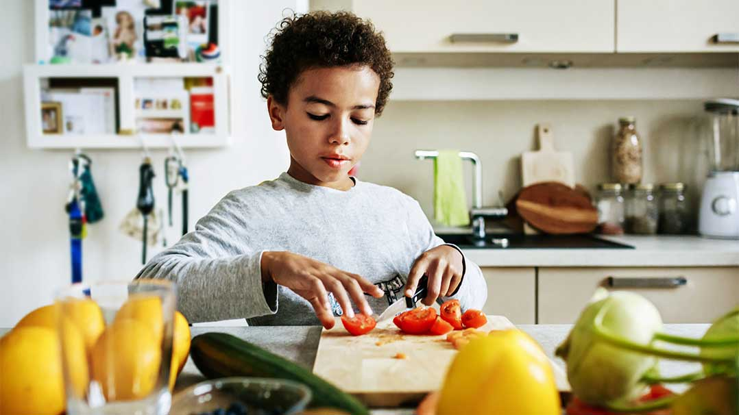 Child cutting up healthy food in kitchen