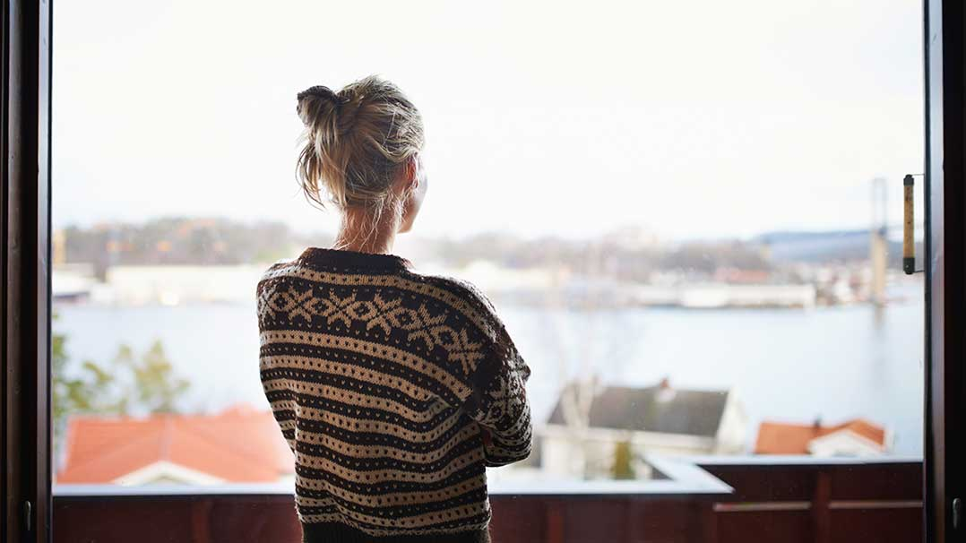 Woman in sweater staring out window