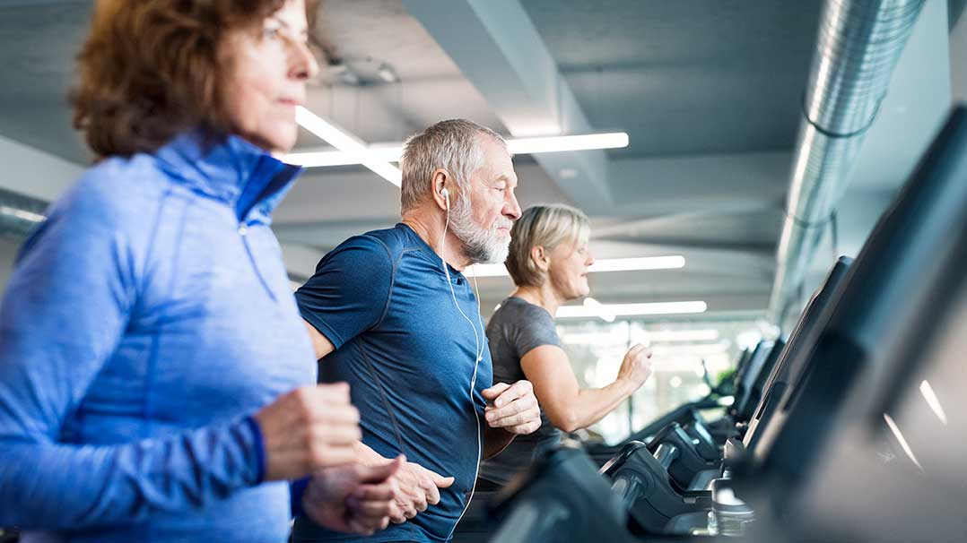 Three older adults stay active by running on treadmills.