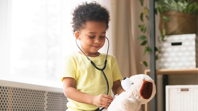 Child playing doctor on stuffed animal