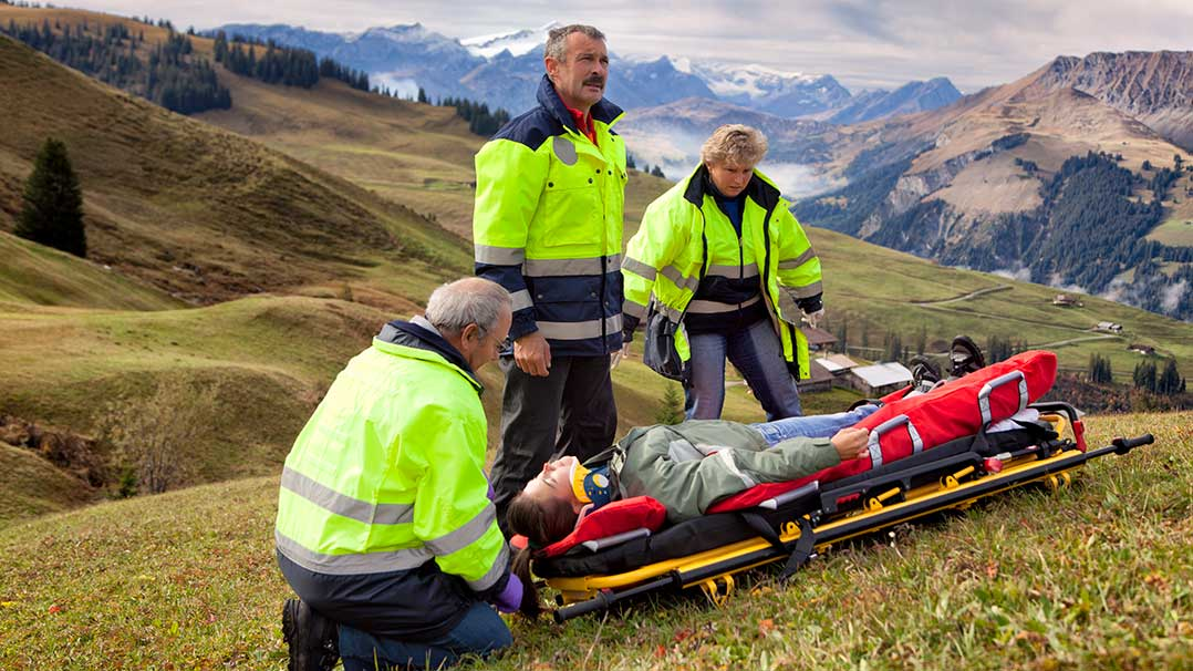 Swiss paramedics team helps an injured young female laying on a stretcher