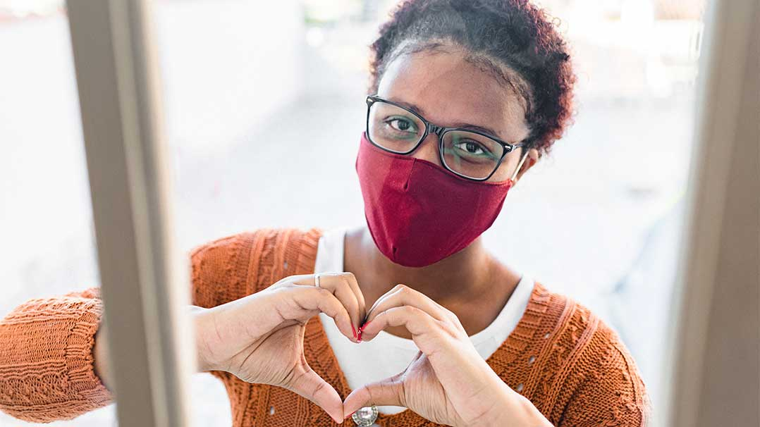Girl wearing mask making a heart with her hands