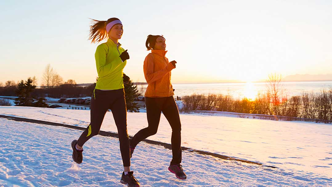 Two young women running in the snow