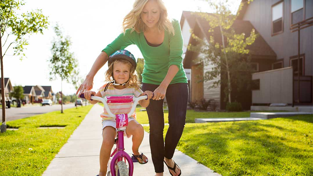 Mom teaching child how to ride bike