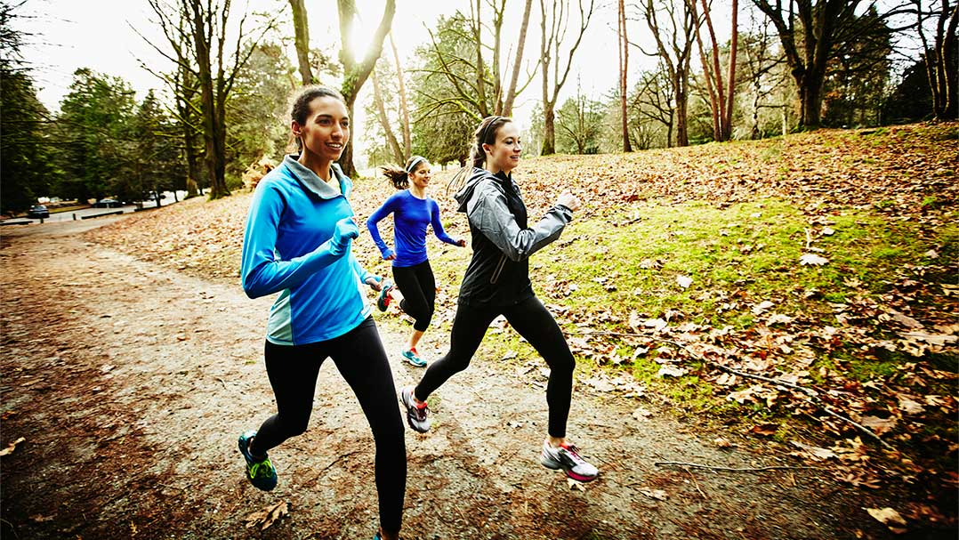 Three teenage girls running in the fall
